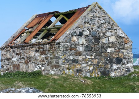 An abandoned stone built byre or barn with only part of the original corrugated iron roof remaing. Cladach Chirceboist, North Uist, Outer Hebrides, Scotland - stock photo