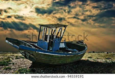 an abandoned wooden fishing boat left to rot away on the shingle beach at dungeness in england with a dramatic sunbeam sky in the background - stock photo