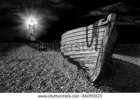 an abandoned wooden fishing boat on a shingle beach illuminated at night by the beam from a lighthouse in black and white - stock photo