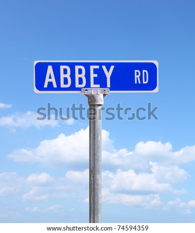 An Abbey road sign against a bright blue cloud filled sky using selective focus and a shallow depth of field with room for your text. - stock photo