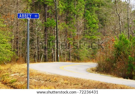 An Abbey road sign along side of a country road honoring the famed Beatles recording studio in London using selective focus. - stock photo