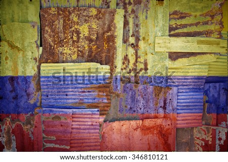 An abstract background image of the flag of Colombia painted on to rusty corrugated iron sheets overlapping to form a wall or fence. - stock photo