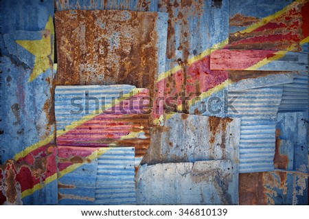 An abstract background image of the flag of Congo Kinshasa painted on to rusty corrugated iron sheets overlapping to form a wall or fence. - stock photo