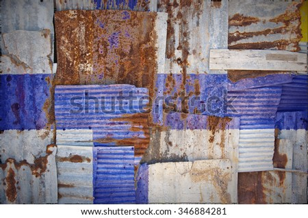 An abstract background image of the flag of Finland painted on to rusty corrugated iron sheets overlapping to form a wall or fence. - stock photo