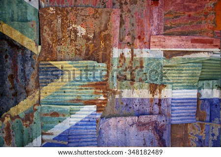 An abstract background image of the flag of South Africa painted on to rusty corrugated iron sheets overlapping to form a wall or fence.