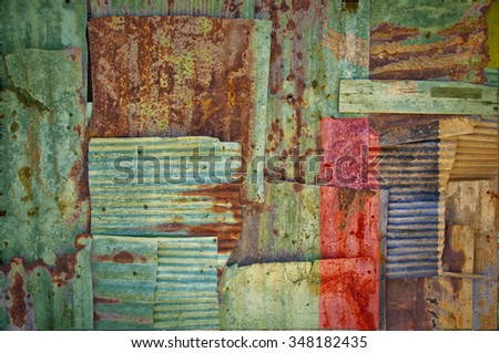 An abstract background image of the flag of Zambia painted on to rusty corrugated iron sheets overlapping to form a wall or fence. - stock photo