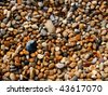 An abstract background of shiny, wet, rounded pebbles on the famous Chesil Beach, part of the Jurassic coastline. - stock photo