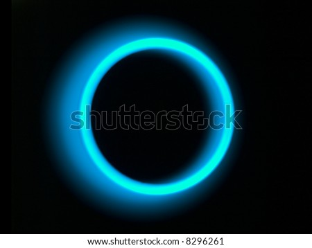 An abstract blue light ring on a dark background. The light is intentionally out of focus and blurred for effect. - stock photo