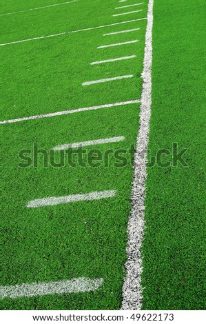 An abstract closeup of an American football field lines on artificial green turf.