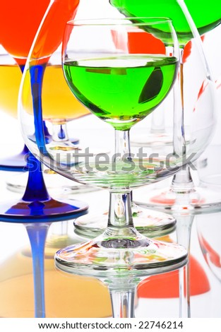 an abstract composition with wine glasses with coloured liquids