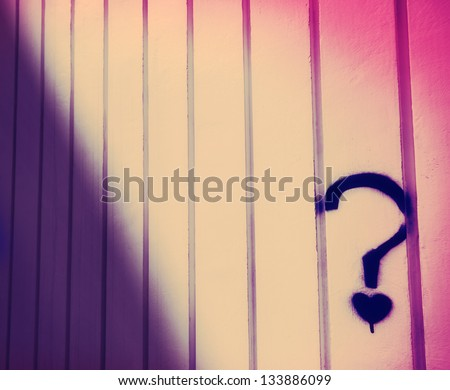 An abstract cross process image of a wall with a spray painted heart under a question mark. - stock photo