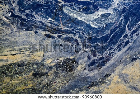 An abstract photograph of an oil spill threatening a fragile wetlands ecosystem.