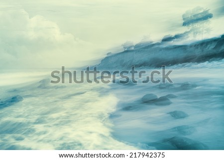 An abstract seascape made with a long exposure and panning motion featuring cross-processed colors. - stock photo