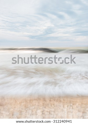 An abstract seascape with blurred panning motion combined with a long exposure.  Image displays soft, desaturated colors. - stock photo