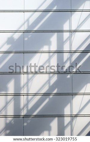 An abstract shadow of a railing and roof structure on a metal cladding / Metal cladding with shadow - stock photo