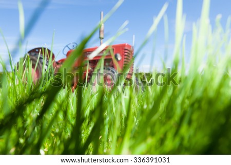 An abstract soft focus shot of an old red tractor in the background and long blades of grass in the foreground.  Implies a farm or the countryside.