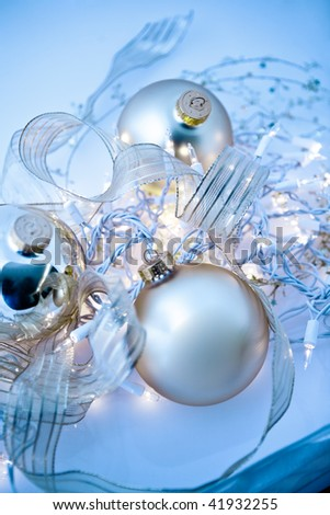 An abstract tangle of glowing silvery Christmas ornaments with translucent ribbons, sparkling gold stars and twinkling white lights. Short depth of field with glowing effects and toned blue. - stock photo