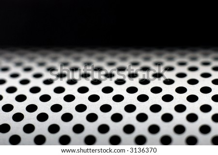An abstract tech compostion showing a perforated curved metal surface in shallow DOF - stock photo