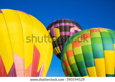 An abstract trio of colorful hot air balloons at launch against a deep blue sky - stock photo