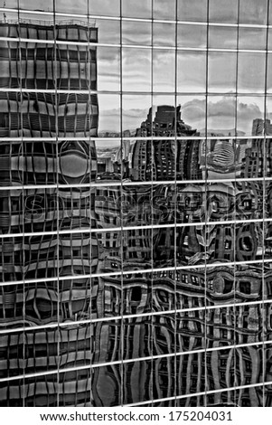 An abstract view of city buildings reflected in glass in grungy black and white. - stock photo
