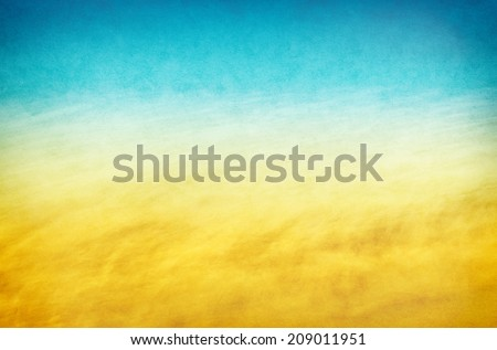 An abstraction of flowing surf and waves with a yellow to blue gradient.  Images displays a pleasing paper grain and texture at 100 percent. - stock photo