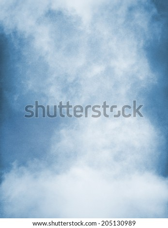 An abstraction of fog and clouds on a textured paper background, toned blue.  Image displays significant paper grain and texture at 100 percent. - stock photo