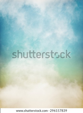 An abstraction of fog and clouds on a textured paper background with a pastel color gradient.  Image displays significant paper grain and texture at 100 percent. - stock photo