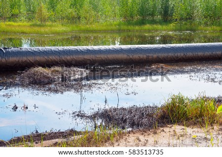 An accident on an oil pipeline. An oil spill around the pipeline. Environmental pollution.