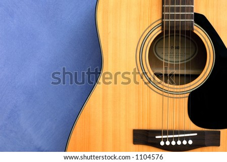 An acoustic guitar in blue background - stock photo