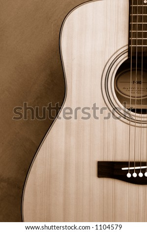 An acoustic guitar in sepia tone - stock photo