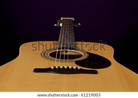 An acoustic natural color guitar isolated against a black background. - stock photo