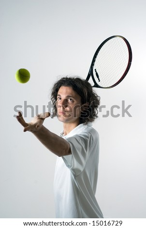 An action shot of a tennis player serving a tennis ball.  The ball is in the air, and the model is staring at it. Vertically framed shot. - stock photo
