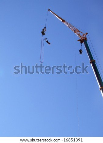 an action sports thrill seeker after jumping from a bungee platform. - stock photo