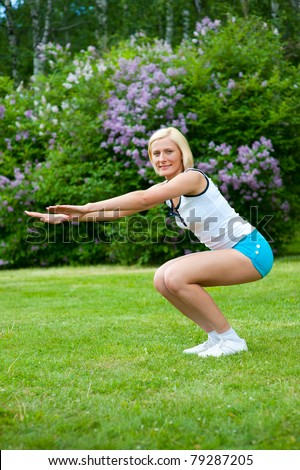 An active beautiful caucasian woman doing sit-ups in the park - stock photo