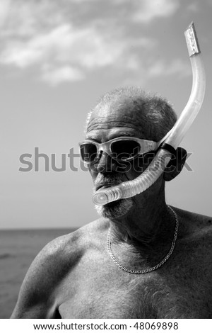 an active retired senior citizen enjoys outdoor and beach activities in black and white - stock photo