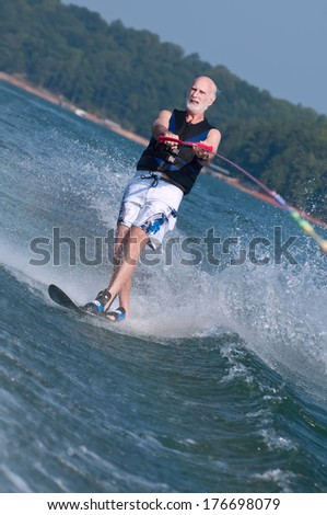 An active senior demonstrates his super fitness on a waterski. - stock photo