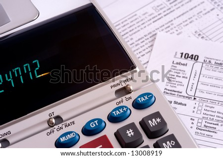 An adding machine or calculator with adding machine tape or paper and tax forms