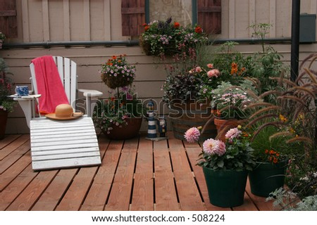 An Adirondack chair on a back yard deck. - stock photo
