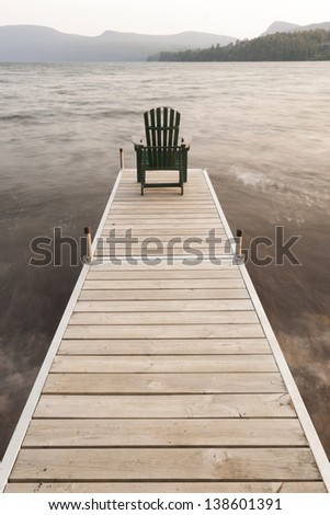 An adirondack chair on a dock at Lake Willoughby, Vermont, USA - stock photo