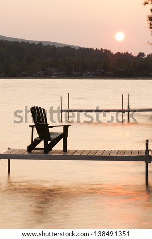 An adirondack chair on a dock at sunset at Lake Willoughby Vermont, USA - stock photo