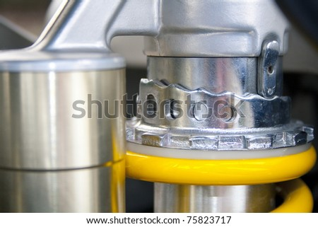 An adjustable rear shock of a modern motorcycle - stock photo