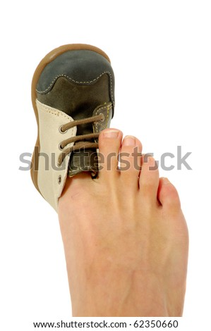 An adolt is trying to fit a baby shoe. - stock photo