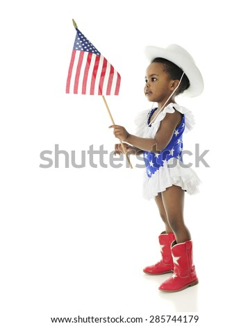 An adorable African American girl looking at the American flag she holds while wearing a red, white and blue majorette outfit.  On a white background. - stock photo
