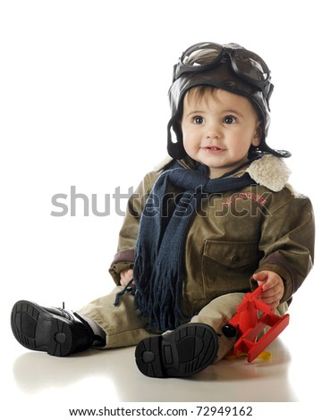 An adorable baby boy holding a toy airplane while wearing an old-fashioned pilot's glasses, hood and goggles.  Isolated on white.