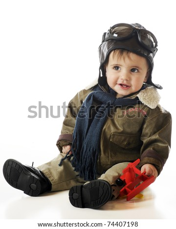 An adorable baby boy in an old-fashioned pilots cap, goggles and jacket while holding a toy airplane.  Isolated on white. - stock photo