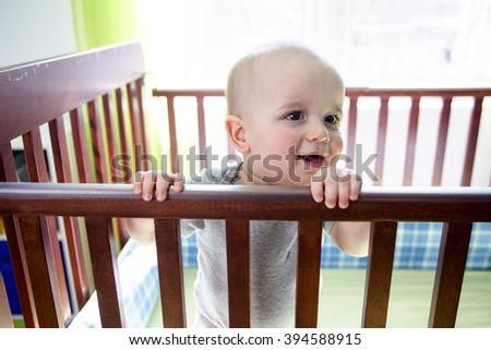 An Adorable baby boy in his crib - stock photo