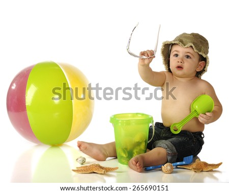 An adorable baby boy in rolled up jeans and hat handing off his sunglasses as he sits among sea shells and beach toys.  Isolated on white. - stock photo