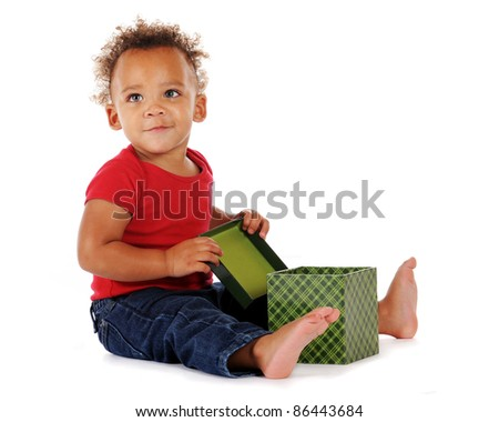 An adorable baby boy looking up, mighty pleased at his opened a gift box.  On a white background.