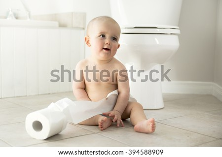 An Adorable baby boy playing with toilet paper - stock photo
