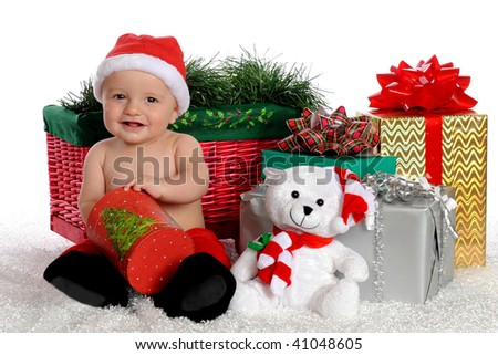 An adorable baby boy reaching inside a round, Christmas box while surrounded by wrapped gifts.  Isolated on white. - stock photo